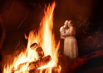 tall timber barn couple standing by campfire